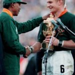 189.  Springbok  captain, Francois Pienaar receiving the rugby world cup trophy from President Nelson Mandela, 24 June 1995 (Mark Baker, Gallo Images)